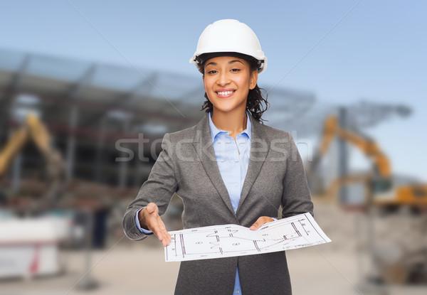 Stock photo: businesswoman in white helmet with blueprint