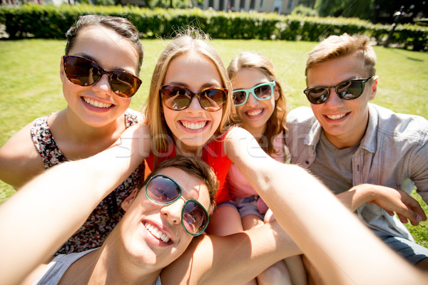 Stock photo: group of smiling friends making selfie in park