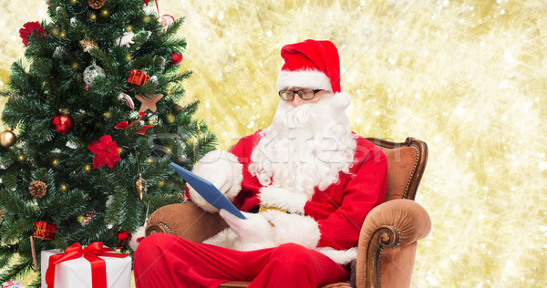 man in costume of santa claus with tablet pc Stock photo © dolgachov