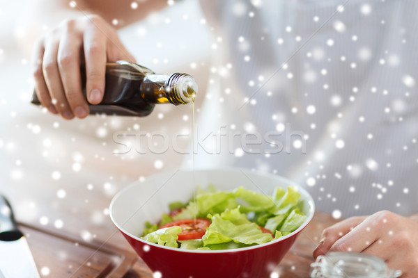 close up of hands flavoring salad with olive oil Stock photo © dolgachov