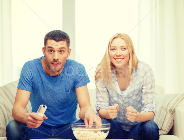 smiling couple with popcorn cheering sports team Stock photo © dolgachov