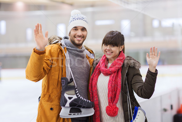 Stock photo: happy couple with ice-skates on skating rink