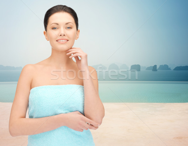 beautiful woman in towel over infinity pool Stock photo © dolgachov