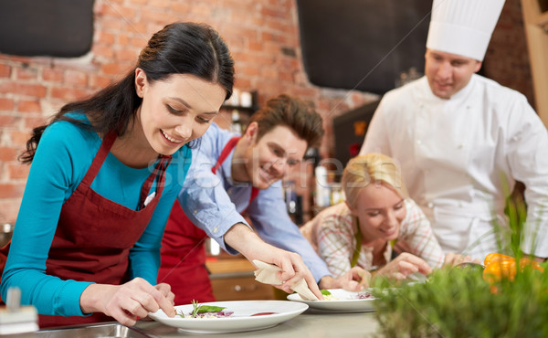 happy friends and male chef cooking in kitchen Stock photo © dolgachov