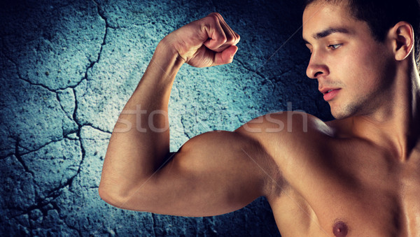 close up of young man flexing and showing biceps Stock photo © dolgachov