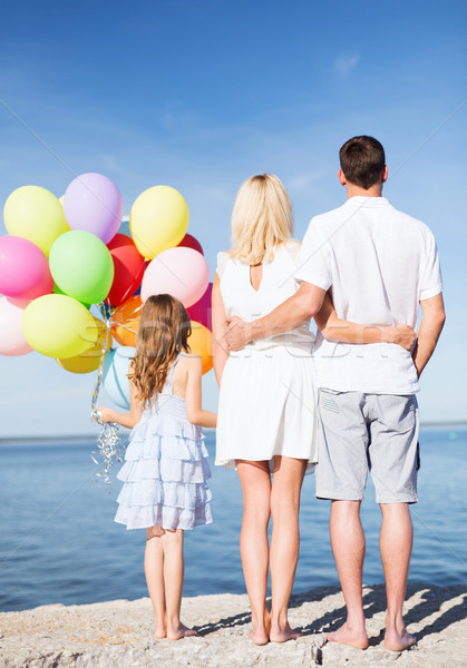 happy family at the seaside with bunch of balloons Stock photo © dolgachov