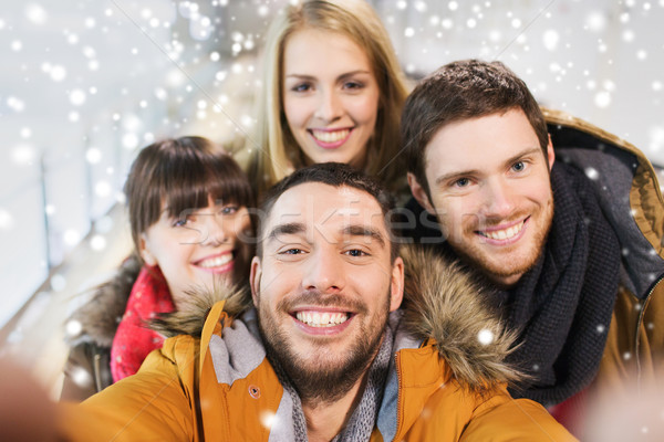 Stock photo: happy friends taking selfie on skating rink