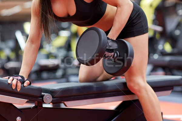 woman flexing muscles with dumbbell in gym Stock photo © dolgachov