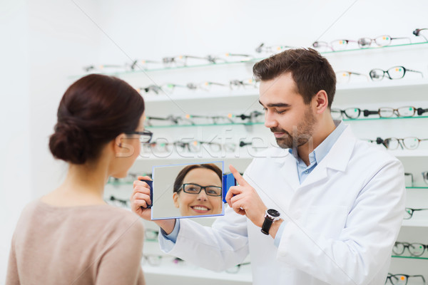 woman in glasses looking to mirror at optics store Stock photo © dolgachov
