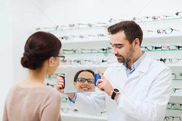 женщину очки глядя зеркало оптика магазине Сток-фото © dolgachov