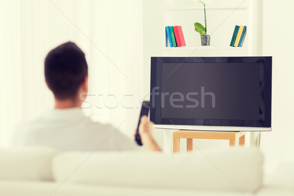 man watching tv and changing channels at home Stock photo © dolgachov