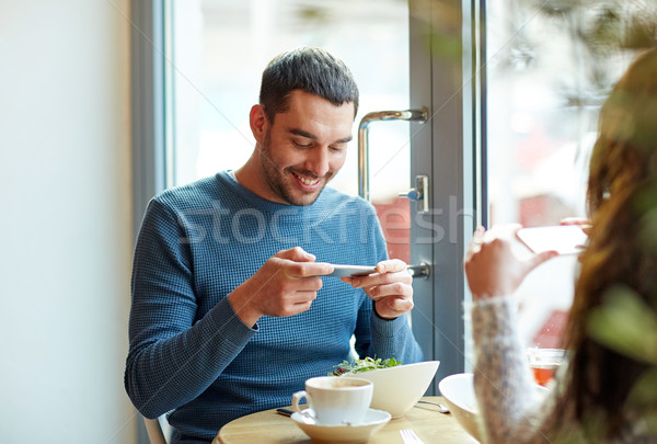 happy couple picturing food by smartphone at cafe Stock photo © dolgachov