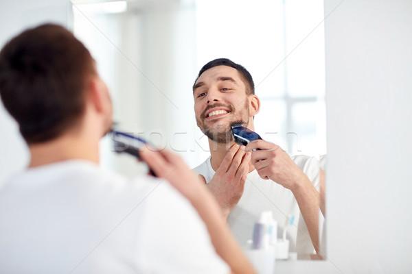 man shaving beard with trimmer at bathroom Stock photo © dolgachov