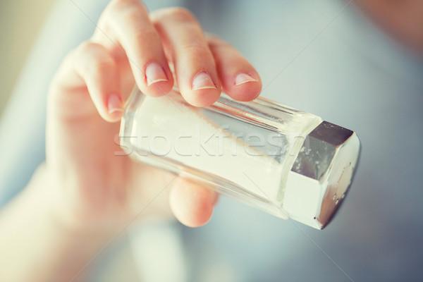 close up of hand holding white salt cellar Stock photo © dolgachov