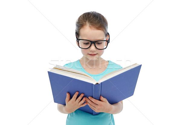 happy little girl in eyeglasses reading book Stock photo © dolgachov