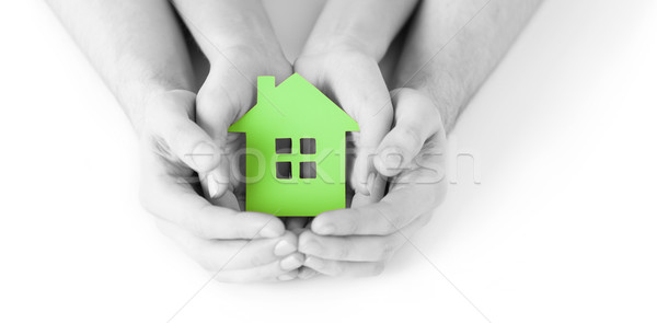 man and woman hands with green paper house Stock photo © dolgachov