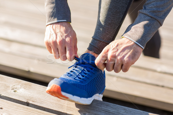 close up of sporty man tying shoe laces outdoors Stock photo © dolgachov