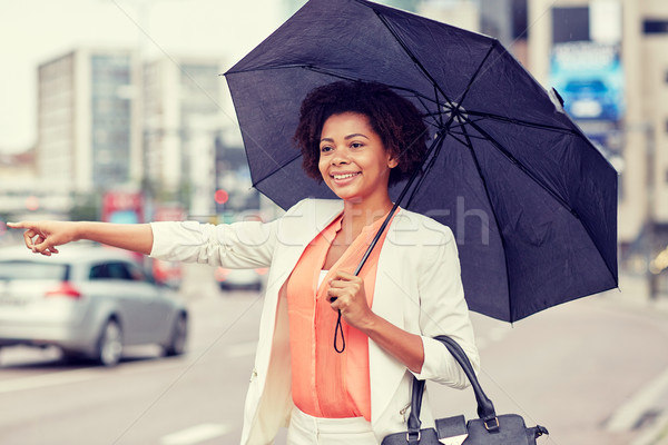 happy african woman with umbrella catching taxi Stock photo © dolgachov