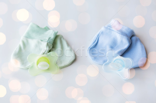close up of baby mittens and soothers for twins Stock photo © dolgachov