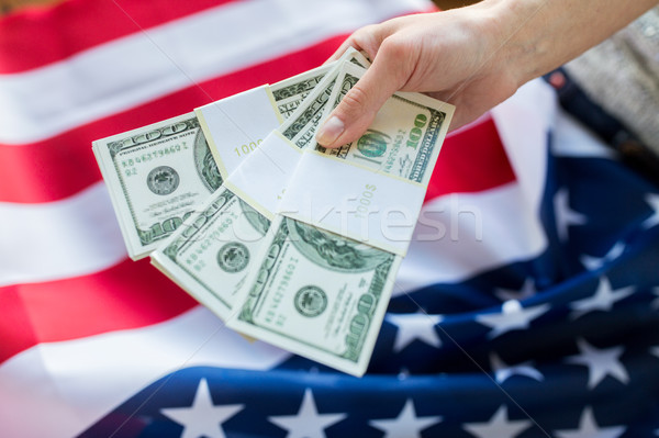 close up of hand with money over american flag Stock photo © dolgachov