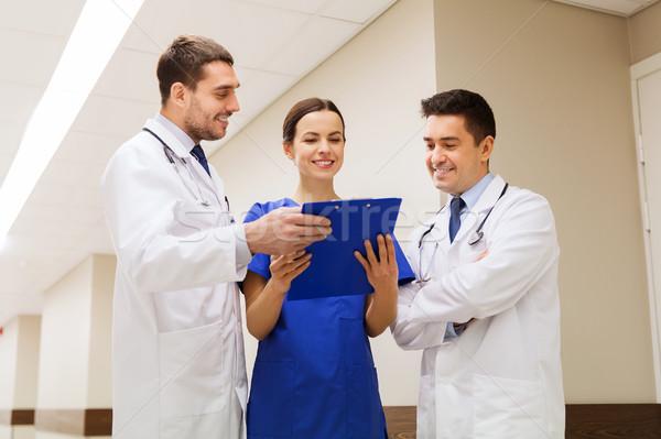 group of happy medics with clipboard at hospital Stock photo © dolgachov
