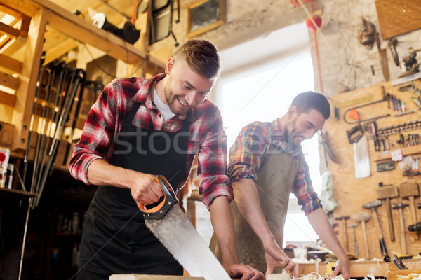 carpenters working with saw and wood at workshop Stock photo © dolgachov