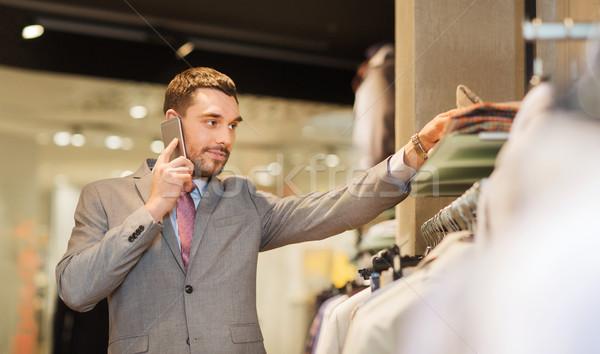 happy man calling on smartphone at clothing store Stock photo © dolgachov