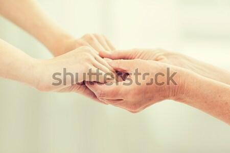 Supérieurs jeune femme mains tenant personnes âge Photo stock © dolgachov