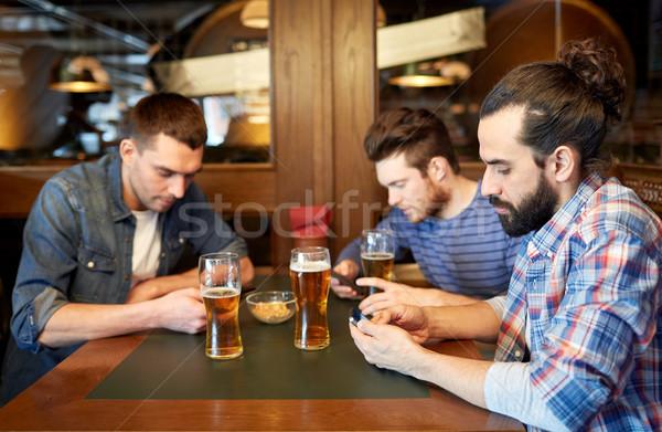 Erkekler akıllı telefonlar içme bira bar birahane Stok fotoğraf © dolgachov