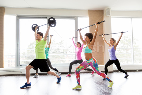 happy people exercising with barbell bars in gym Stock photo © dolgachov