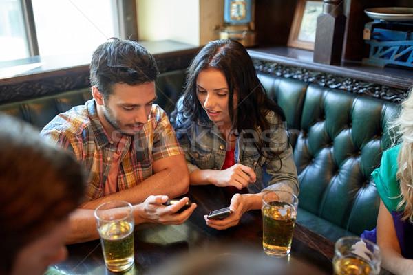 Amigos smartphones cerveza bar pub personas Foto stock © dolgachov