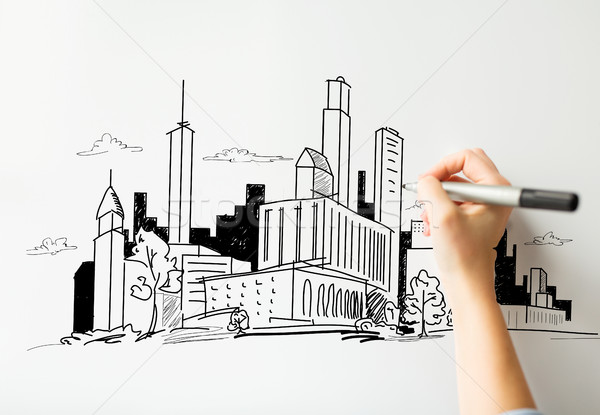 close up of hand drawing city on white board Stock photo © dolgachov