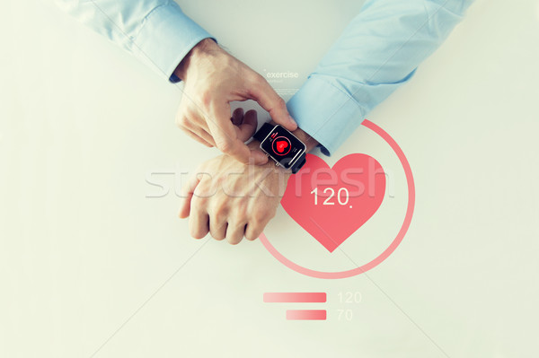close up of hands with heart icon on smart watch Stock photo © dolgachov