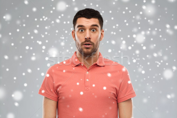 surprised man in polo t-shirt over snow background Stock photo © dolgachov