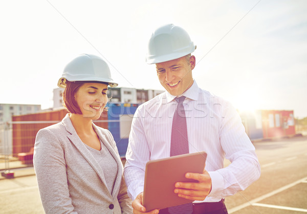 happy builders in hardhats with tablet pc outdoors Stock photo © dolgachov