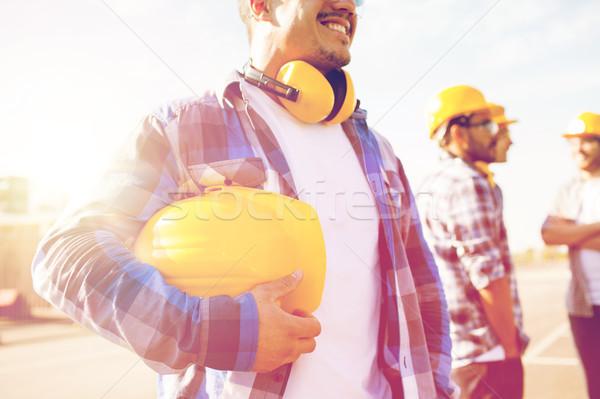 Közelkép építész tart munkavédelmi sisak épület viselet Stock fotó © dolgachov