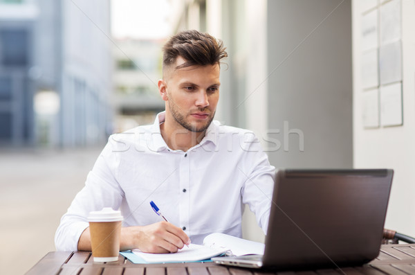 man with laptop and coffee at city cafe Stock photo © dolgachov