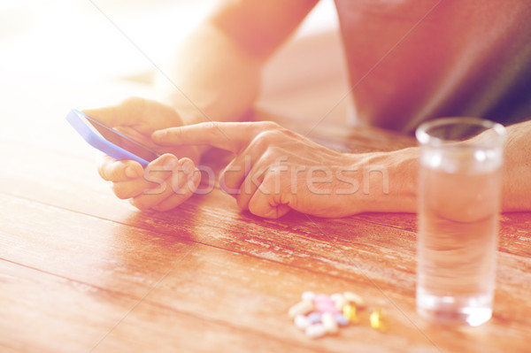 close up of hands with smartphone, pills and water Stock photo © dolgachov