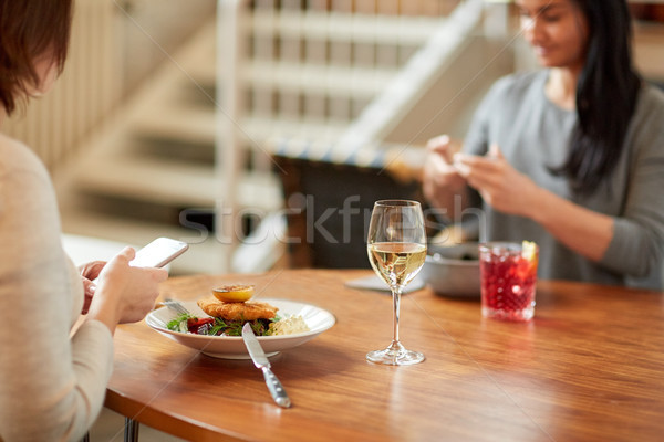 women with smartphones and food at restaurant Stock photo © dolgachov
