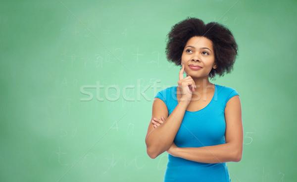 pensive afro american  woman over green chalkboard Stock photo © dolgachov