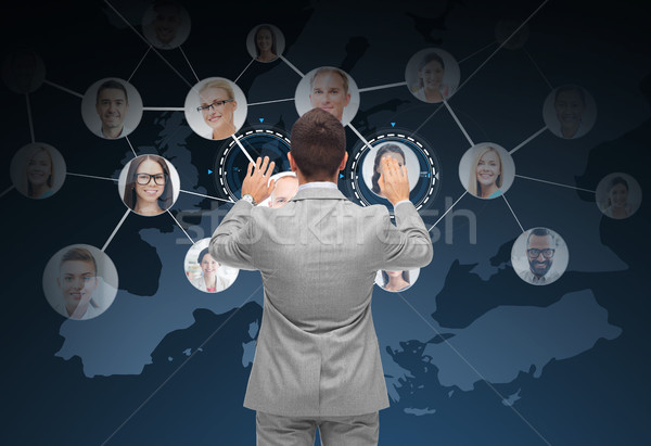 Stock photo: businessman using virtual screen with contacts