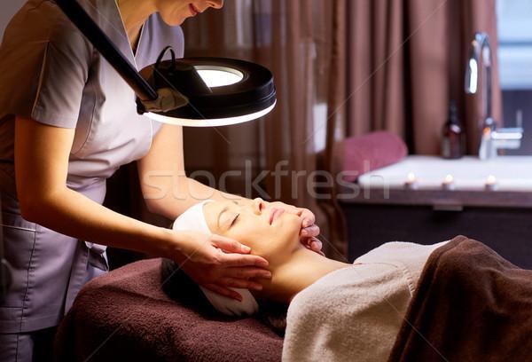 beautician doing face massage to woman at spa Stock photo © dolgachov