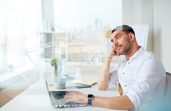 businessman with laptop thinking at office Stock photo © dolgachov
