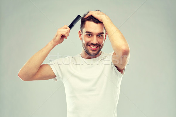 happy man brushing hair with comb over gray Stock photo © dolgachov