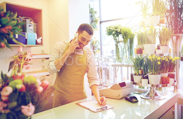 man with smartphone making notes at flower shop Stock photo © dolgachov