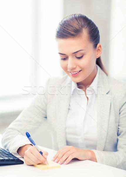 businesswoman writing on sticky note Stock photo © dolgachov