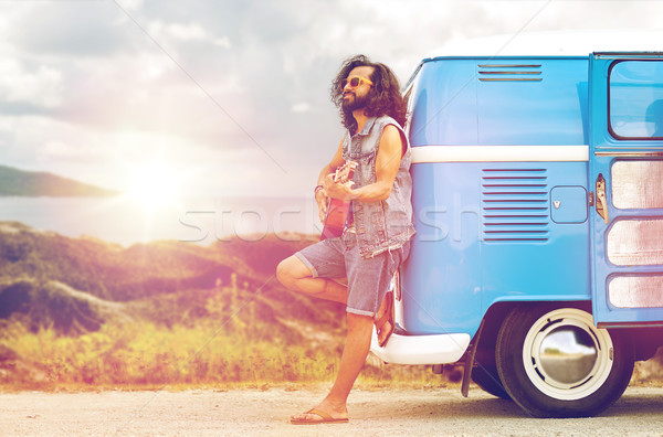 hippie man playing guitar at minivan car on island Stock photo © dolgachov