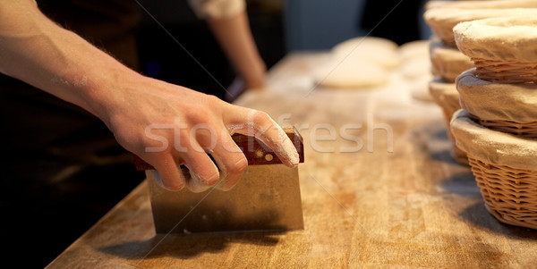 baker portioning dough with bench cutter at bakery Stock photo © dolgachov