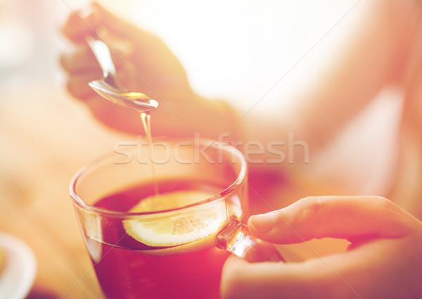 close up of woman adding honey to tea with lemon Stock photo © dolgachov