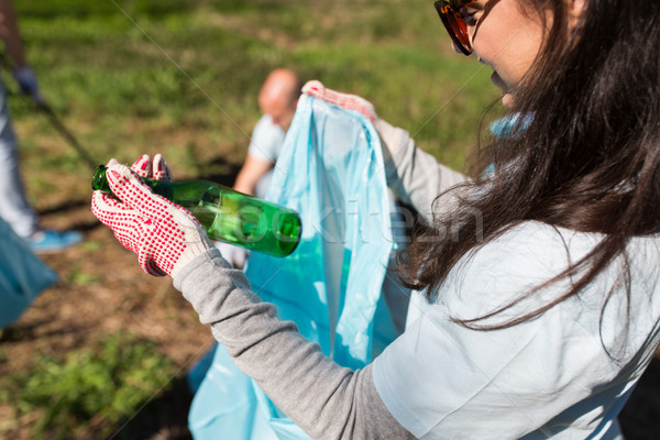 volunteer with trash bag and bottle cleaning area Stock photo © dolgachov